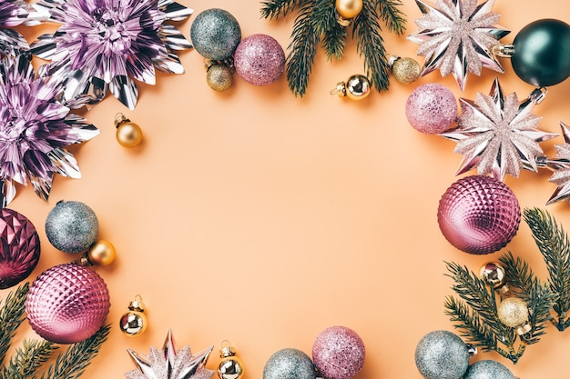 Накладные состав новогоднего фона. круглая рамка из блестящих украшений и безделушек на светлом фоне с копией пространства