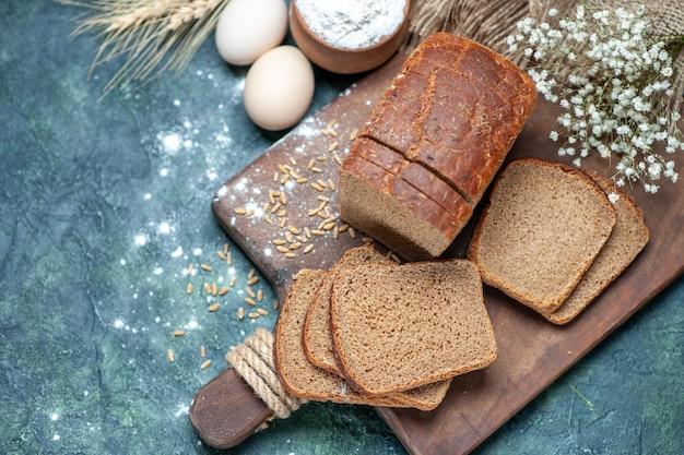 Sovraccarico di grano di pane nero dietetico su tavola di legno picchi di farina di uova di fiori in una ciotola su sfondo blu