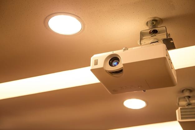 회의실 천장에 장착 된 오버 헤드 디지털 프로젝터.