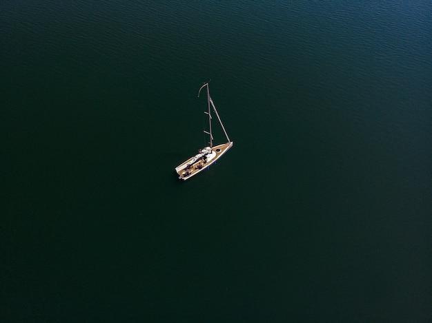 Фотография парусной лодки на берегу красивого озера в солнечный день с дронов