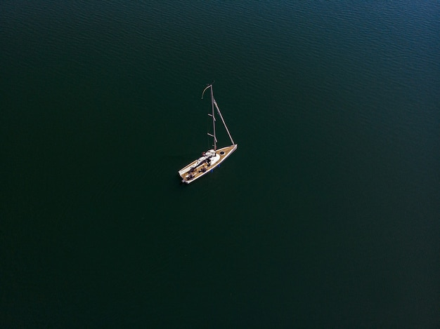 Overhead drone photography of a sailing boat in a beautiful lake on a sunny day