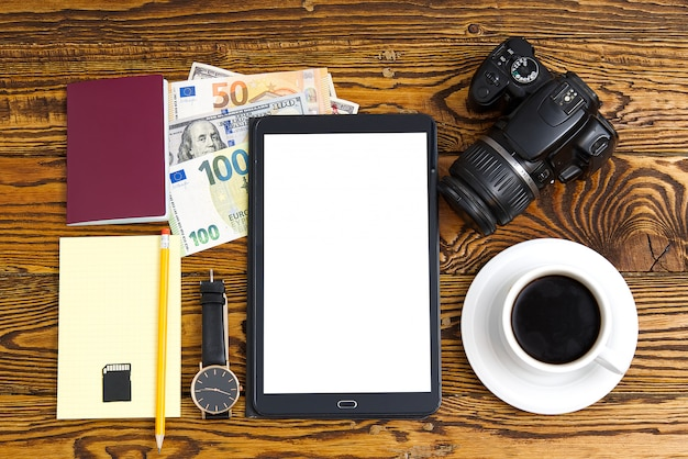 Overhead of essentials for modern young person. different objects on wooden table. travel concept. passport, camera, money, tablet, coffee