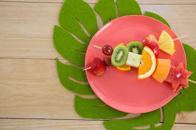 Overhead of fruit skewers in plate on wooden table