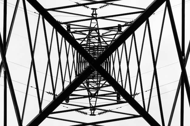 Under overhead high-voltage power line tower. view from bottom of construction