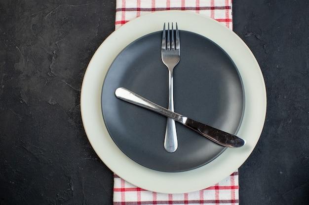 여유 공간이 있는 검정색 배경에 빨간색 벗겨진 수건에 짙은 회색 색상과 흰색 빈 접시에 설정된 칼 붙이 머리 위