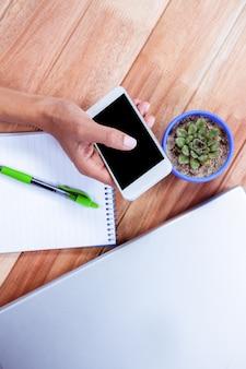 テーブル上のノートパソコンとノートパソコンでスマートフォンを持っている女性の手のオーバーヘッド