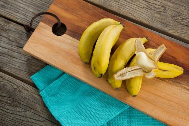 木製のテーブルのまな板に新鮮なバナナのオーバーヘッド