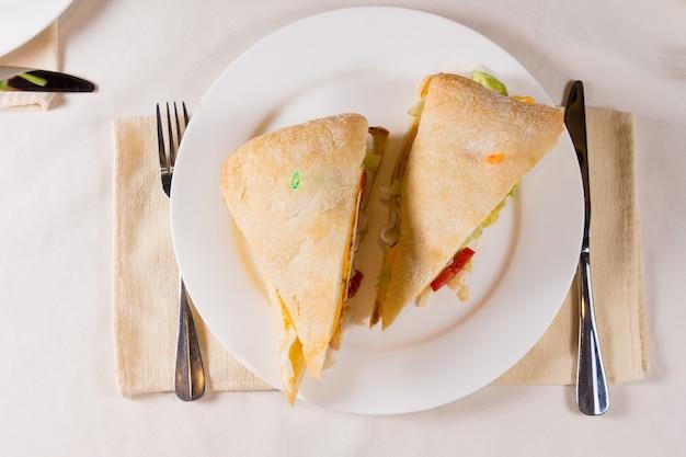 レストランの場所の設定でプレート上の正方形のチャバタパンのサンドイッチのオーバーヘッド