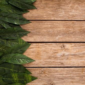 ボーダーの葉とコピースペースを持つ木製の板の背景のオーバーヘッド
