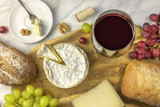 An overhead photo of a glass of red wine with cheese