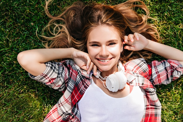 人生を楽しんでいる白人のデボネアの女の子のオーバーヘッド写真。緑の草の上に横たわっている大きなヘッドフォンでポジティブな白人女性。