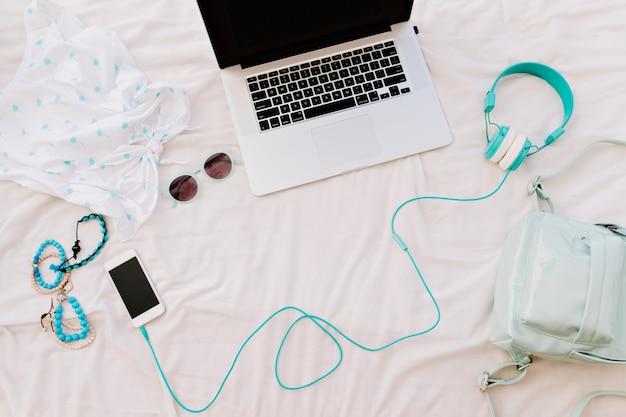 Фотография сверху модных браслетов, смартфона, ноутбука и наушников, лежащих рядом с женской рубашкой и солнцезащитными очками. кто-то забыл на кровати наушники, сумку и аксессуары.