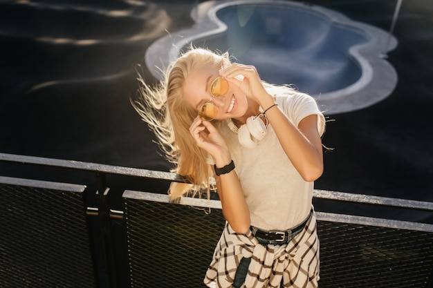 Overhead photo of stunning caucasian woman looking through yellow sunglasses.