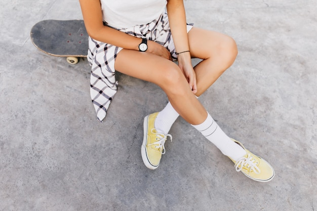 Overhead photo of tanned caucasian woman chilling in skate park after training. magnificent woman wears white socks and yellow shoes sitting on skateboard.