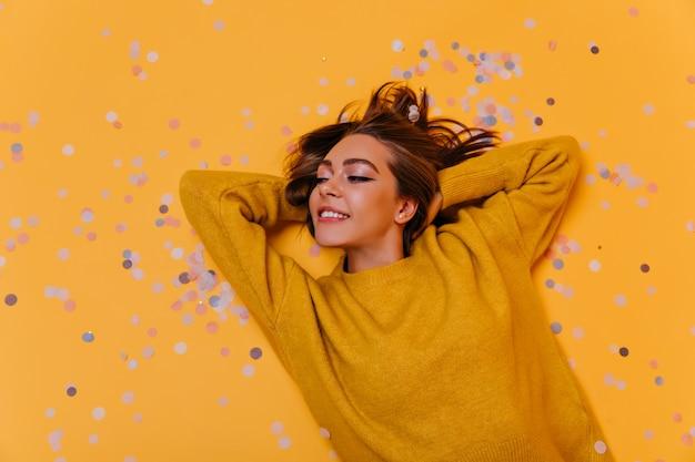 Ritratto ambientale di attraente donna sdraiata su coriandoli viola. tiro al coperto di sorridente ragazza rilassata in posa sulla parete gialla.