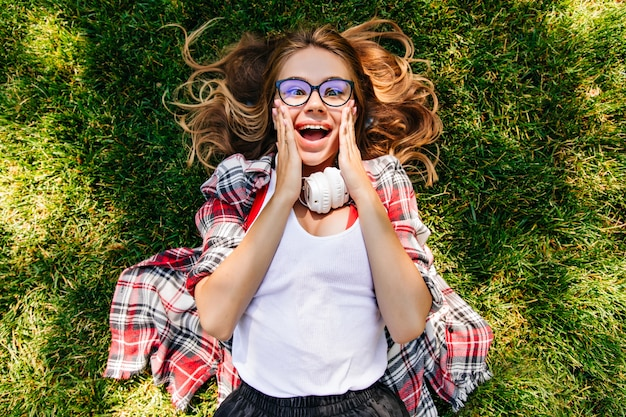 Overhead portrait of emotional girl posing on the ground with surprised smile. funny blonde lady lying on grass in park.