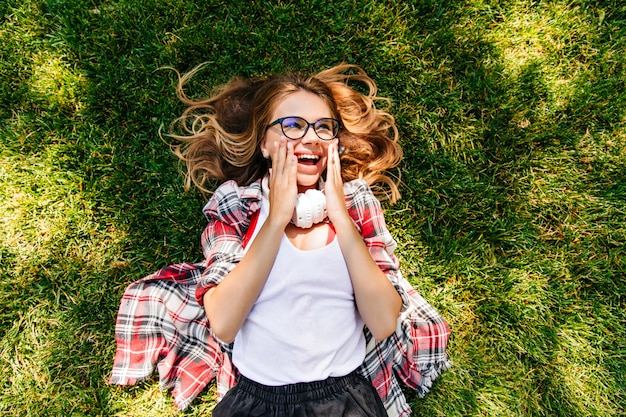 Overhead portrait of glad caucasian girl lying on grass. relaxed adorable lady chilling in summer day.