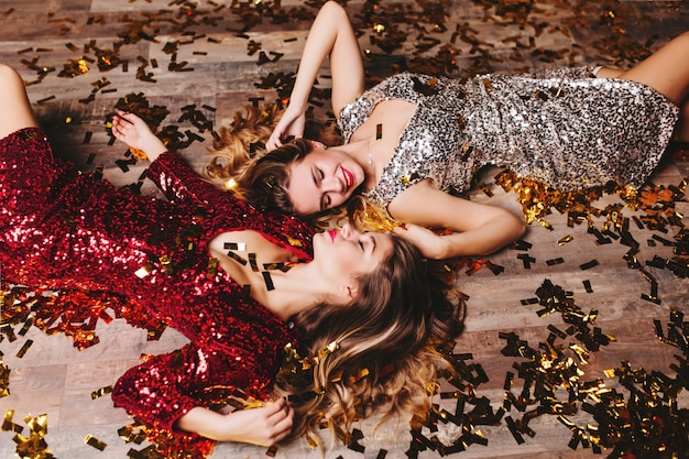 Overhead portrait of inspired women wears sparkle attires cute smiling, while resting after new year party
