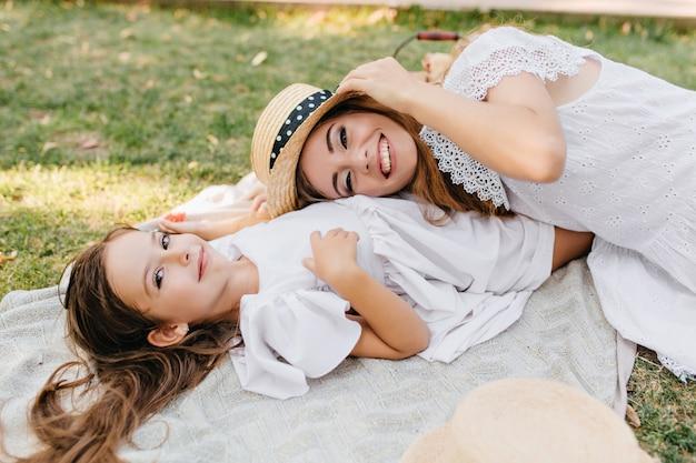 Ritratto ambientale della donna che ride sdraiato sulla pancia della figlia dopo il picnic. ragazza beata dai capelli scuri in vestito bianco divertendosi con il lunedì che si rilassa sull'erba nel fine settimana.