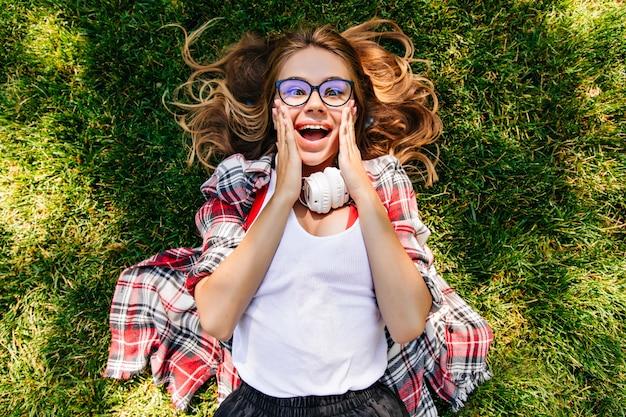 驚いた笑顔で地面にポーズをとる感情的な女の子のオーバーヘッドの肖像画。公園の草の上に横たわっている面白いブロンドの女性。