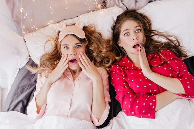 枕の上に横たわっている見事な女の子のオーバーヘッドの肖像画。ベッドで冷やしている驚いた白人女性の屋内ショット。