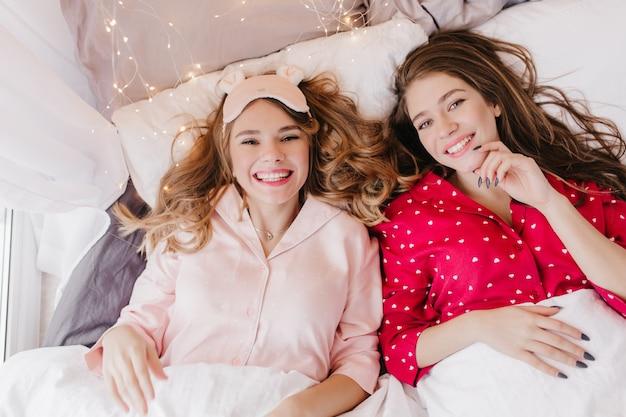 ベッドで身も凍る2人の魅力的な白人の女の子の頭上の肖像画。かわいいナイトスーツを着た可愛い姉妹の室内写真。