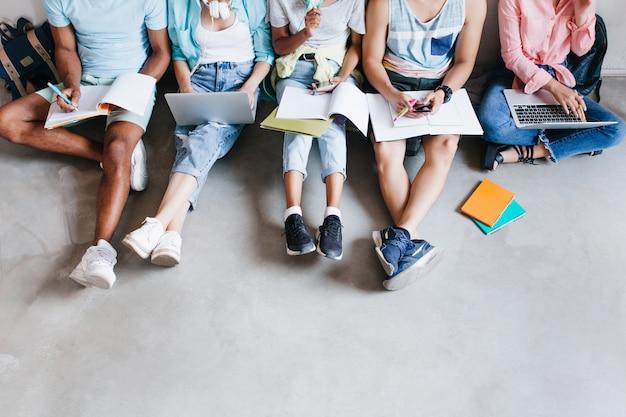 노트북 및 스마트 폰, 바닥에 함께 앉아 젊은 사람들의 오버 헤드 초상화. 무릎에 교과서를 들고 강의를 쓰는 학생들.