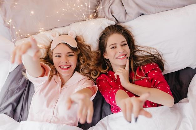 Ritratto ambientale di due ragazze accattivanti sdraiate a letto e sorridenti. donna riccia in maschera per gli occhi rosa in posa con piacere al mattino.