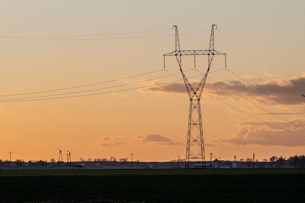 Overhead power line in the countryside at sunset