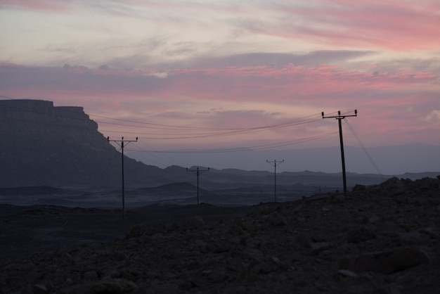 曇りの夕焼け空の下の谷の架空送電線