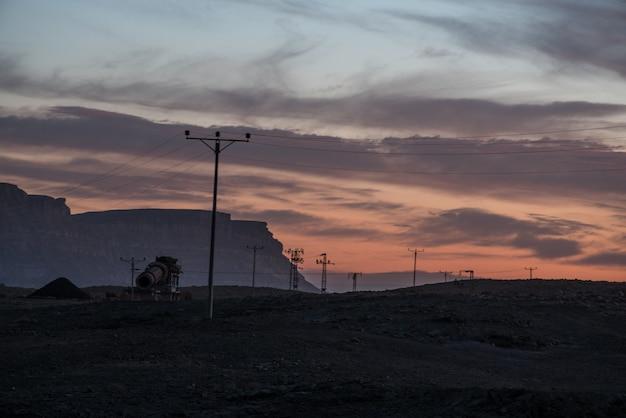 曇り夕焼け空の下の谷の架空送電線