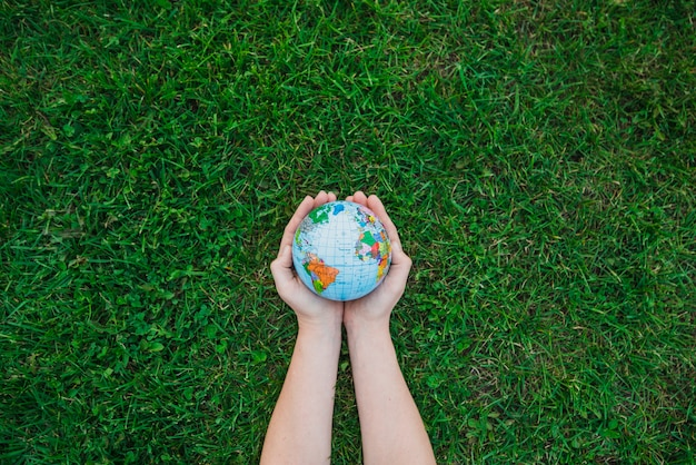 An overhead's view of hands holding globe over green grass