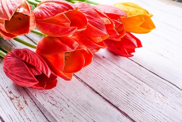 素朴な木のテーブルの上にオレンジと黄色のチューリップの花束を頭上で撃ちました。フラットレイオーバーヘッドビュースタイル。ギフトの概念を受け入れる