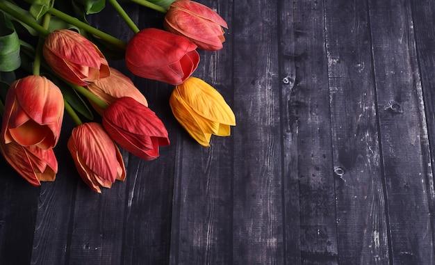 オーバーヘッドは、素朴な木のテーブルの上にオレンジと黄色のチューリップの花束を撮影