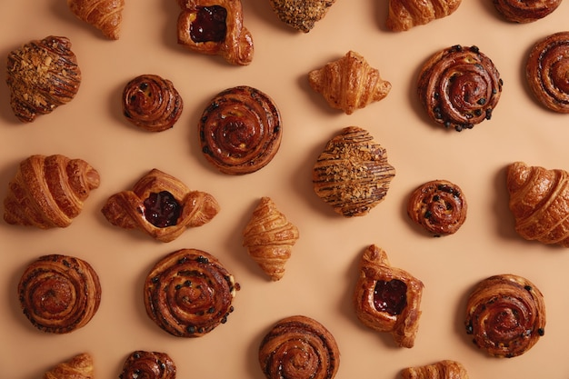 Overhead shot of appetizing delicious sweet confectionery products containing much sugar which can cause obesity and chronical diseases. various croissants, buns and swirls to choose in bakers shop