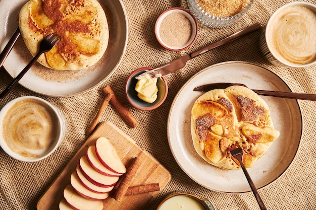 Overhead shot of apple pancakes coffee apples and other ingredients on a table