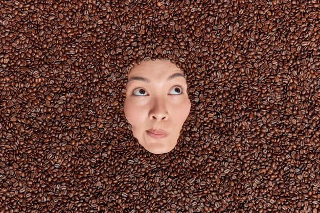 Overhead shot of asian woman shows only face through coffee beans containing much caffeine which helps to improve your memory and mental functoning. female model around tasty treat