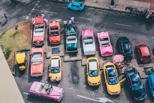 Overhead shot of assorted cars in different colors in a parking lot