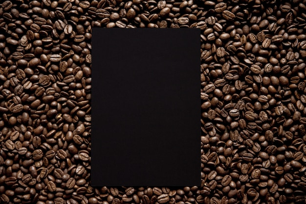 Overhead shot of a black square in the middle of coffee beans great for writing text