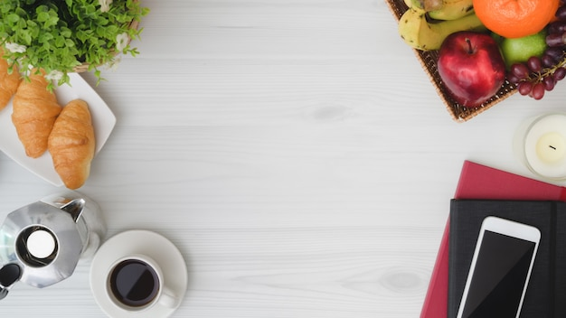 Overhead shot of  breakfast table with copy space, phone, notebook, fruit basket, croissant, coffee cup and moka pot