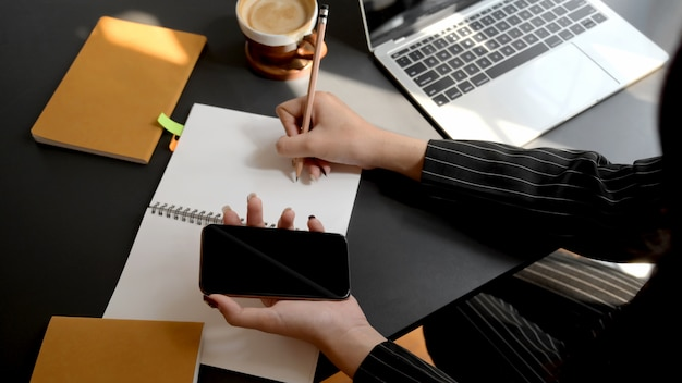 Overhead shot of businesswoman writing on notebook while using smartphone in comfortable workplace