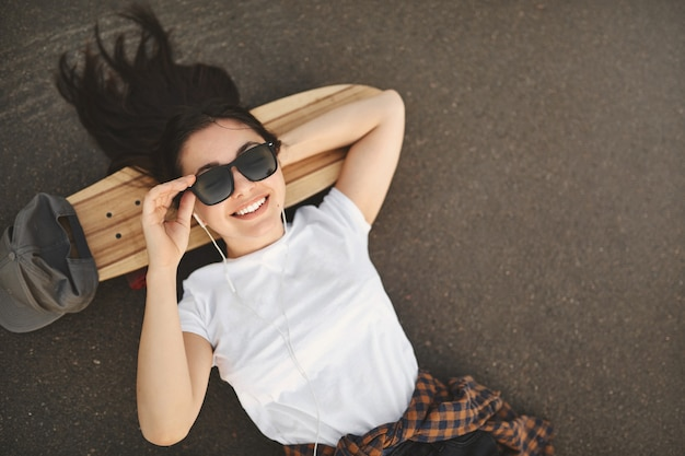 Overhead shot carefree teenage girl lying on concrete at skatepark