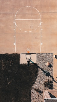 Overhead shot of a cement basketball field with the hoop and rocks