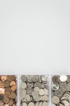 Scatto dall'alto di centesimi in contenitori isolati su un muro grigio