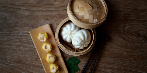 Overhead shot of chinese steamed dumpling and steamed pork bun in a bamboo steamer with chopstick
