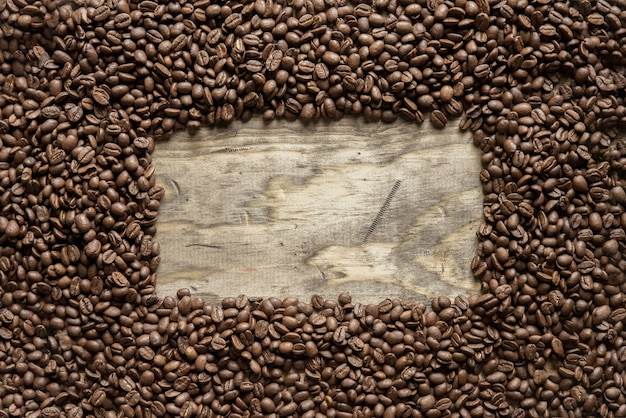 Overhead shot of a coffee beans frame over a wooden surface great for background or writing text