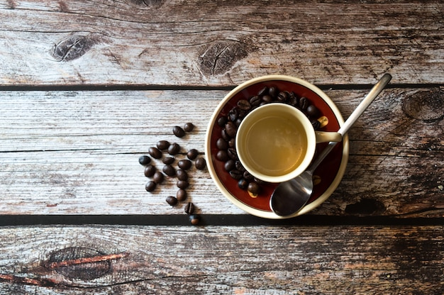 Overhead shot of a coffee cup near coffee beans and a metal spoon on a wooden surface