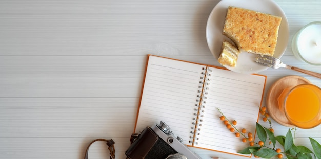 Overhead shot of cozy workspace with blank notebook with toast bread and a glass of orange juice