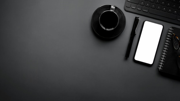 Overhead shot of dark modern workspace with copy space, blank screen smartphone and office supplies