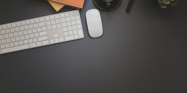 Overhead shot of dark trendy workspace with office supplies with copyspace